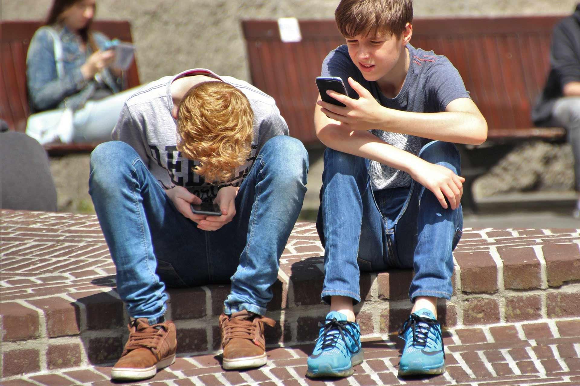 Nens consultant el mòbil al carrer